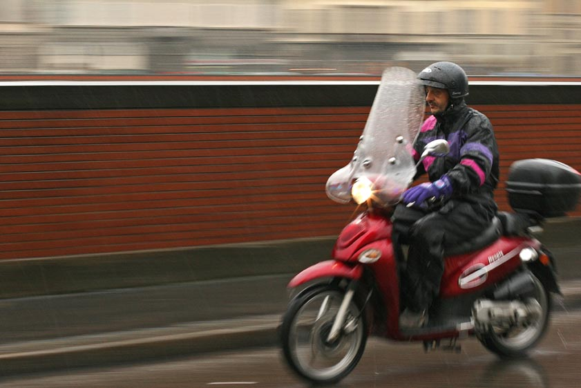 Image of a motorcycle moving through Florence is an example the panning technique